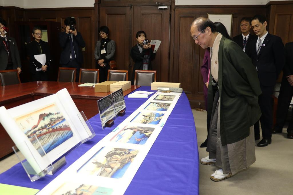 復刻された絵巻に見入る門川市長(手前)=京都市中京区