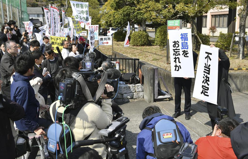 「不当決定」などのメッセージを掲げる住民側関係者=15日午前、山口地裁岩国支部前
