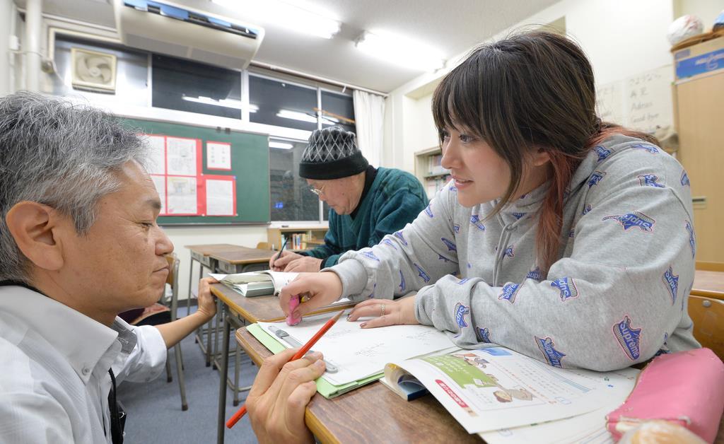 尼崎市立成良中琴城分校の数学の授業で、教諭(左)に教えられながら問題を解く大永尉惠さん(右)=30日午後、兵庫県尼崎市(安元雄太撮影)