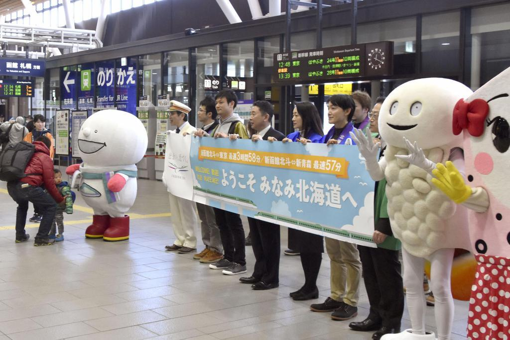 北海道新幹線で新函館北斗駅に到着した乗客を迎える関係者ら=16日午後、北海道北斗市