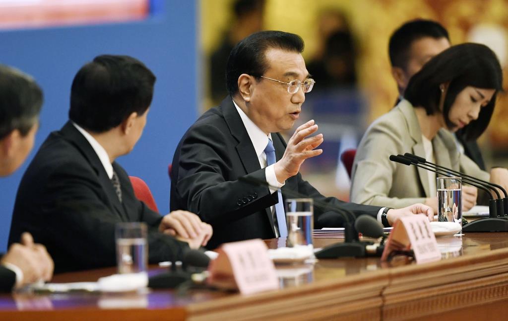記者会見する李克強首相(中央)=15日、北京の人民大会堂(共同)