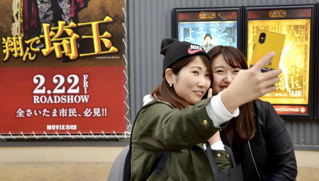 「翔んで埼玉」を見た後、映画館を背に記念撮影する女性=さいたま市