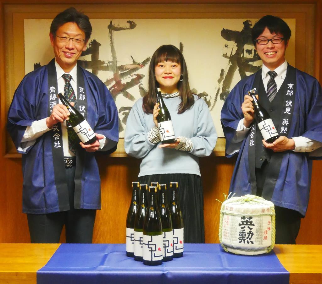新しいラベルの日本酒「英勲 鬼ころし」を手に取る齊藤社長(左)と池川さん(中央)=京都市左京区