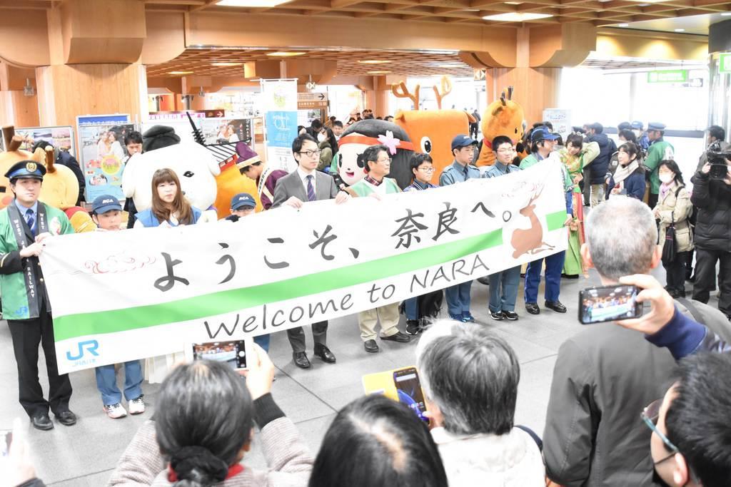 新大阪駅からJR奈良駅を結ぶ「直通快速」の乗客を県内自治体キャラクターなどが出迎えた=奈良市のJR奈良駅