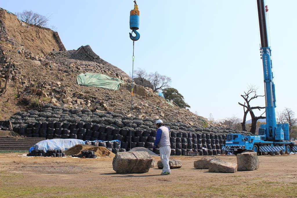 クレーン車を用いて、崩落した石垣が一つ一つ下に降ろされた=香川県丸亀市