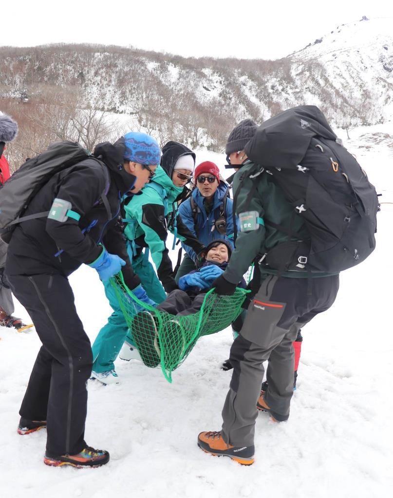 雪上での負傷者搬送を訓練する講習会参加者。奥は茶臼岳=17日、栃木県那須町