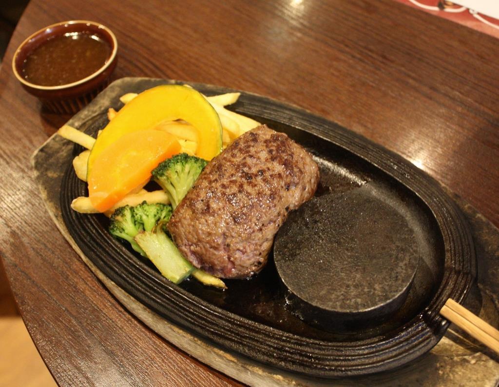 名物の「村上牛のレアハンバーグ」。中身のレアの部分を、丸い焼き石で焼いて食べる。自家製のガーリックソースとの相性も抜群