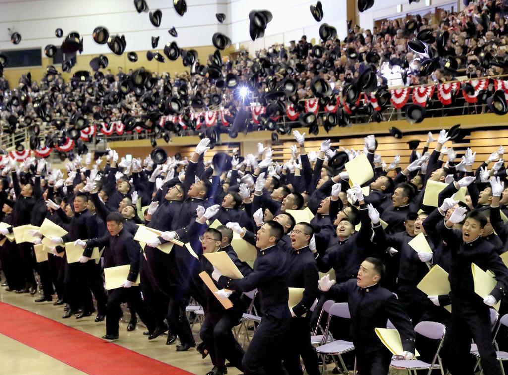 防衛大学校の卒業式を終え、帽子を投げる卒業生=17日午前、神奈川県横須賀市