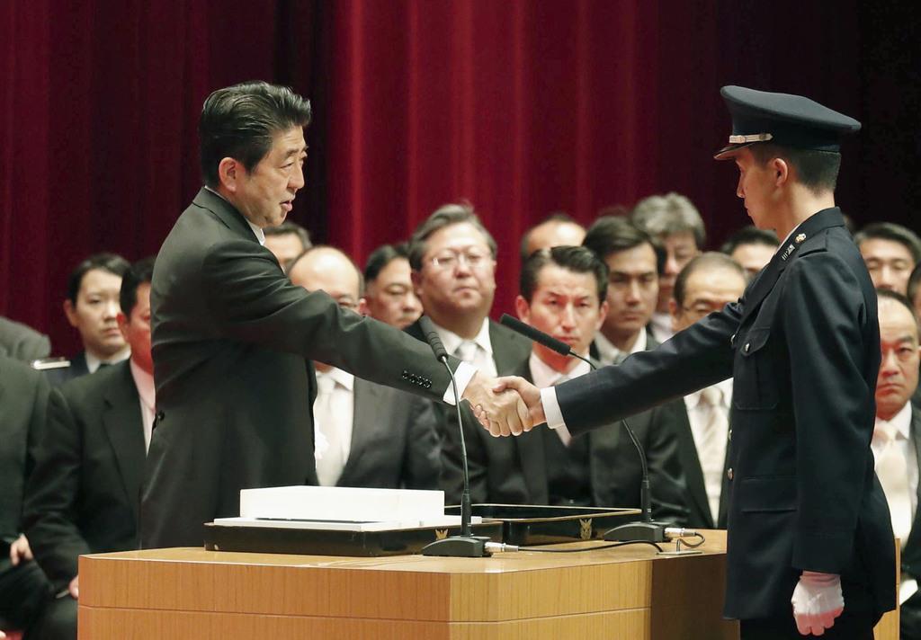 防衛大学校の卒業生と握手する安倍晋三首相=17日午後、神奈川県横須賀市