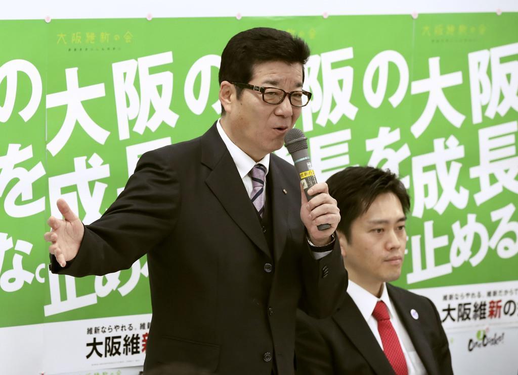 8日、大阪維新の会の会合であいさつする松井一郎大阪府知事(左)。自身が市長選に、吉村洋文大阪市長(右)が知事選にそれぞれ入れ替わって立候補すると表明した=大阪市