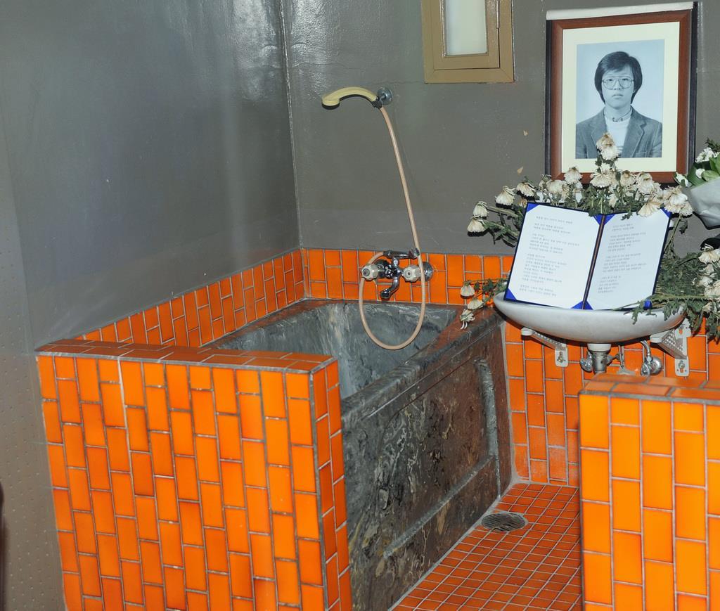 朴鍾哲さん(右上の遺影)が拷問死した治安本部対共分室の取調室。左の浴槽が「水責め」の拷問で使われた=2012年2月、ソウル(共同)