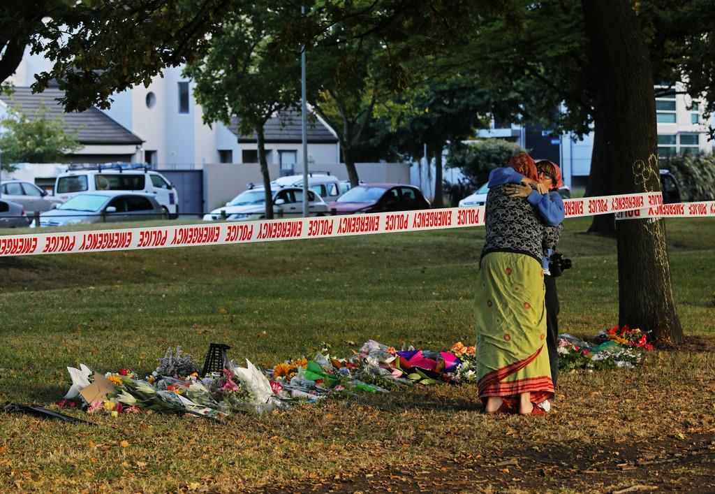 襲撃された2つのモスクのうちのひとつ、マスジッド=アル・ノル・モスクの前で抱擁する女性ら=17日、クライストチャーチ(AP)