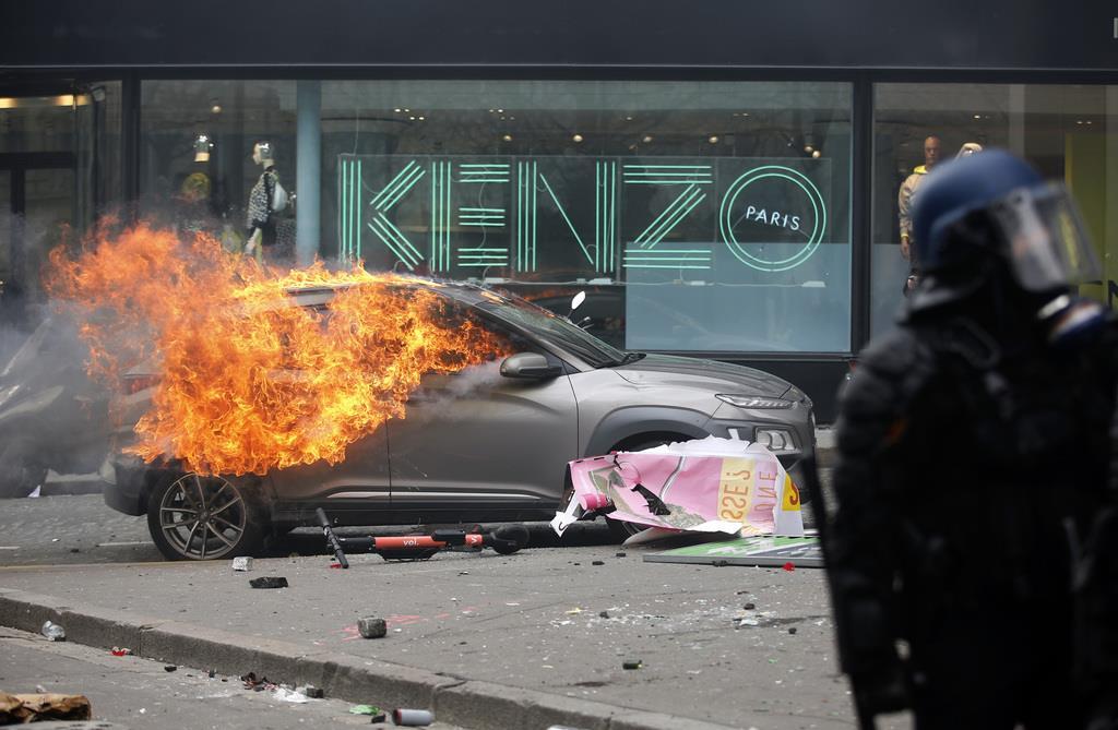 週末デモで、炎上する車のそばに立つ警察官=16日、パリ(AP)