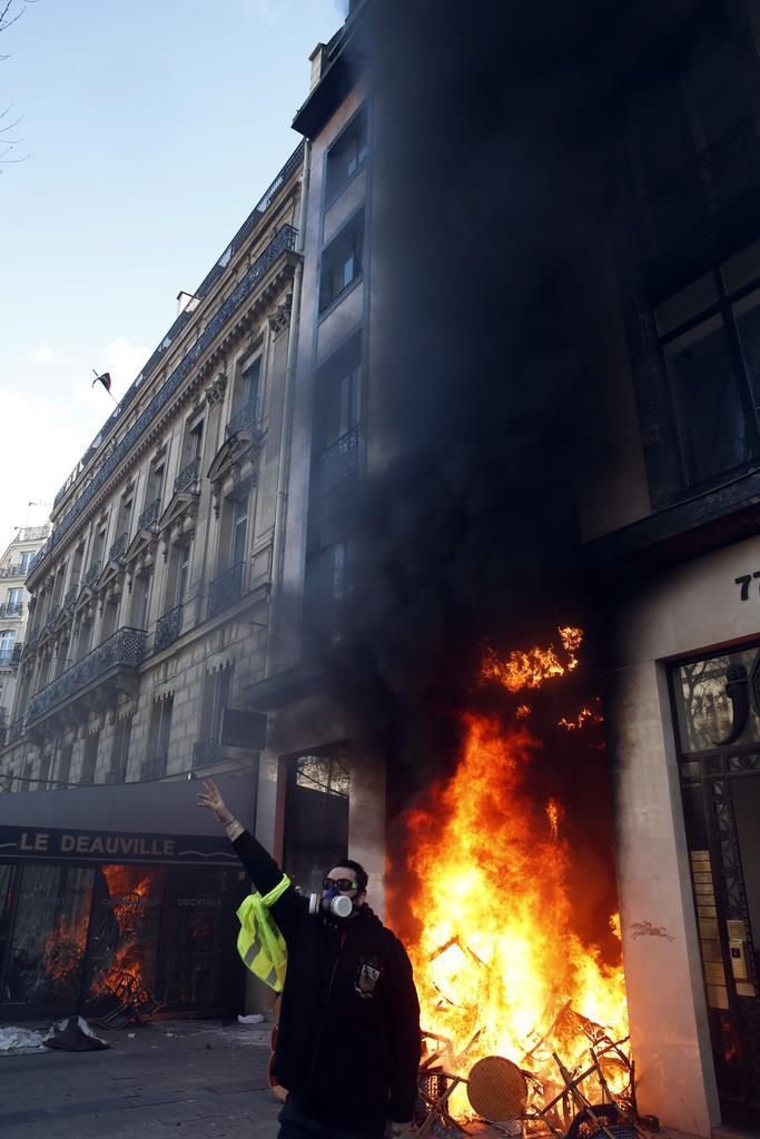 週末の「黄色いベスト」デモで、放火され、煙を上げる建物=16日、パリ(AP)