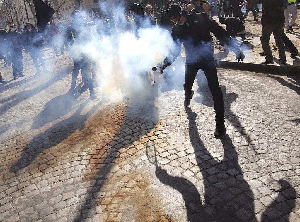 「黄色いベスト」デモに向けて警官隊が投げた催涙ガスを投げ返すデモ隊の男性=16日、仏パリ(ロイター)