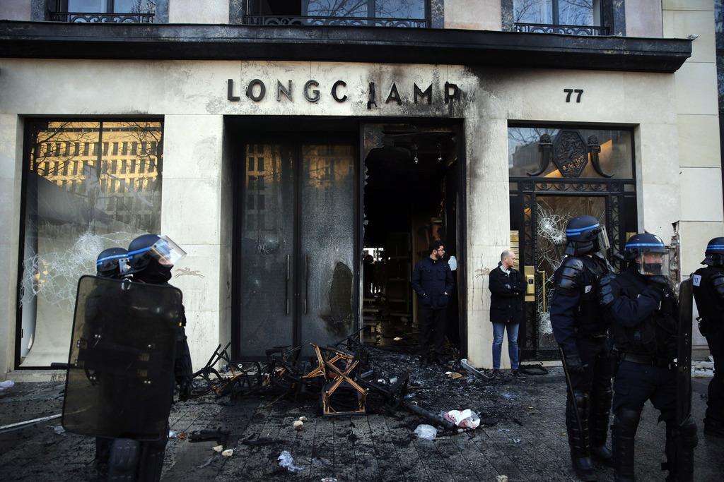 週末デモで放火された店舗の前に立つ警察官ら=16日、仏パリ(AP)