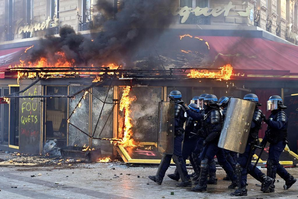 16日、パリのシャンゼリゼ大通りで、デモ隊が火を付けた老舗の高級カフェ「フーケッツ」(ゲッティ=共同)