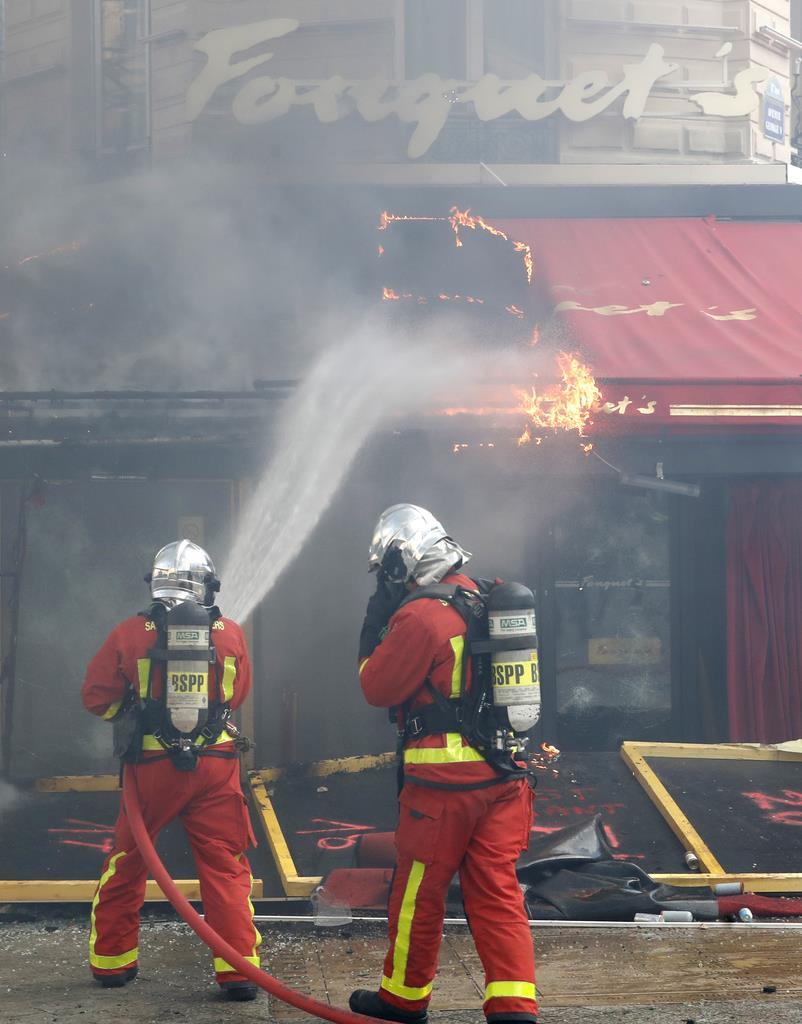 「黄色いベスト」運動のデモ隊の一部に放火された有名カフェ「フーケッツ」の消火活動に当たる消防関係者=16日、仏パリのシャンゼリゼ通り(AP)