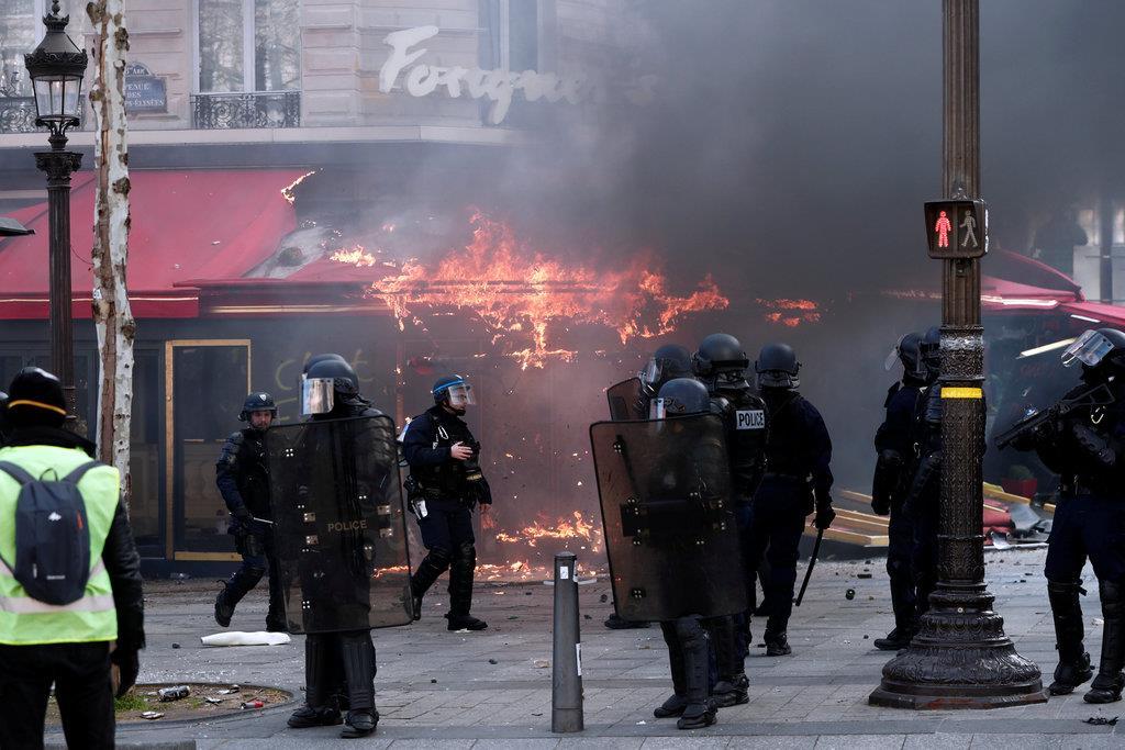 「黄色いベスト」運動のデモ隊に放火され、炎上する有名カフェ「フーケッツ」=16日、仏パリのシャンゼリゼ通り(ロイター)