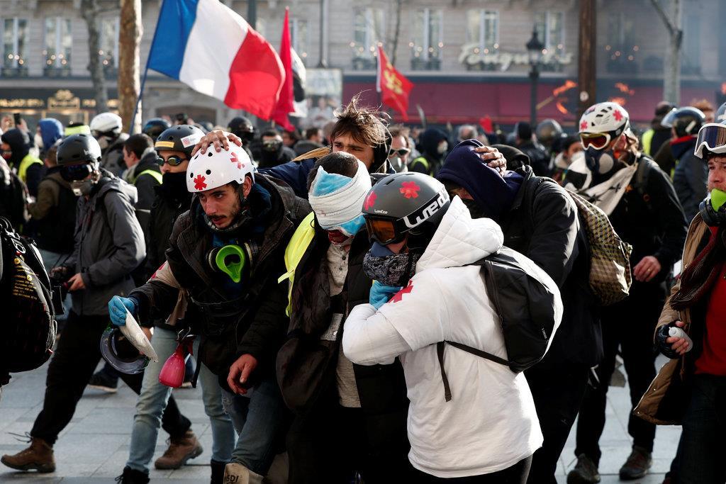 「黄色いベスト」運動のデモ隊が通過する中、医療関係者に付き添われる人=16日、仏パリのシャンゼリゼ通り(ロイター)