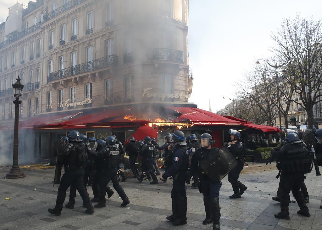 「黄色いベスト」運動のデモ隊に放火され、炎上する有名カフェ「フーケッツ」=16日、仏パリのシャンゼリゼ通り(AP)