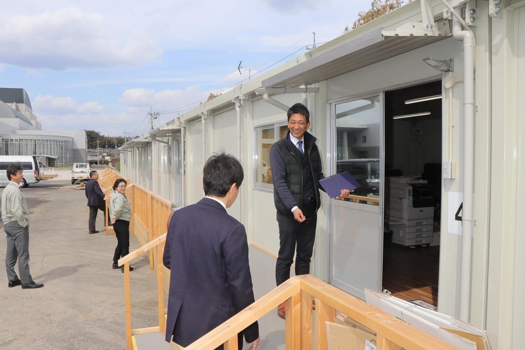 開店1号店となった保険代理店で、来客を迎える菊池達也さん=岡山県倉敷市