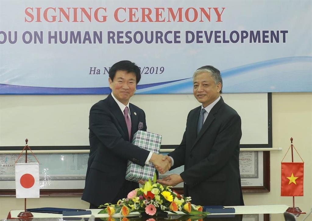介護人材確保に関する覚書を締結後、ベトナムの担当副大臣と握手を交わす千葉県の森田健作知事(左)=14日、ベトナム・ハノイ(同県提供)