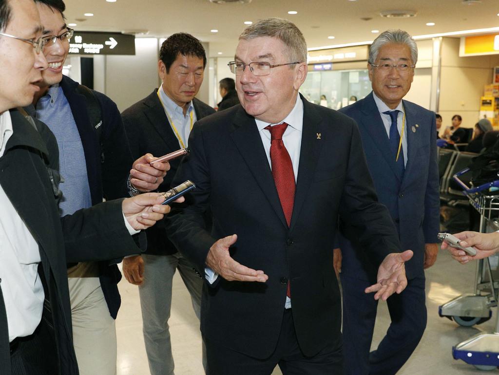 2018年11月、成田空港で取材に応じるIOCのトーマス・バッハ会長(中央)と、出迎えたJOCの竹田恒和会長(右端)