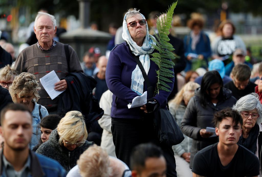 21日、ニュージーランド・クライストチャーチで、銃乱射テロ犠牲者の追悼集会に参加する女性(ロイター)