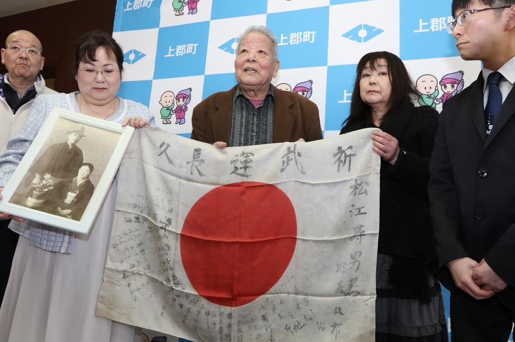 74年ぶりに返還された日章旗を持つ松江実男さん(中央)ら=上郡町役場