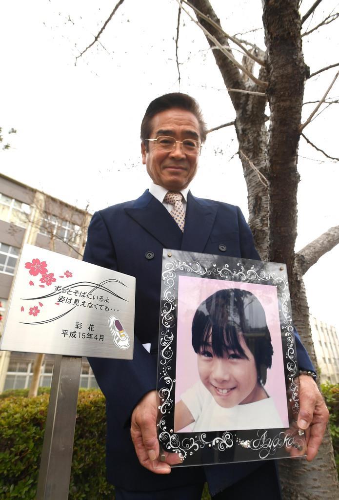 神戸連続児童殺傷事件から22年が経ち、16年前に植樹された「彩花桜」のそばに新しいプレートが設置された。亡くなった彩花ちゃんの写真を持つ父親の山下賢治さん=23日午後、神戸市須磨区(柿平博文撮影)