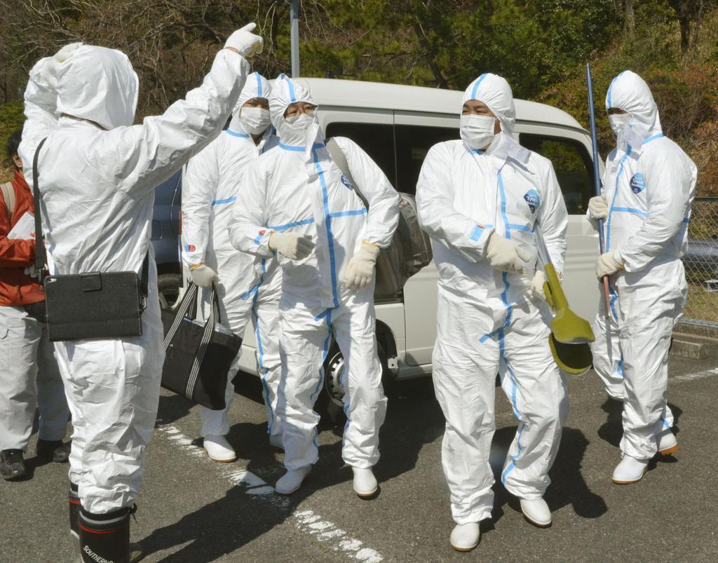 野生イノシシを媒介とした豚コレラの感染拡大防止のため、ワクチン入りの餌の埋設に向かう作業員=24日午前、愛知県小牧市