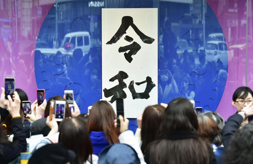東京・銀座の「和光」前で、書家が揮毫した新元号「令和」の書をスマホで撮影する人たち=1日午後1時1分