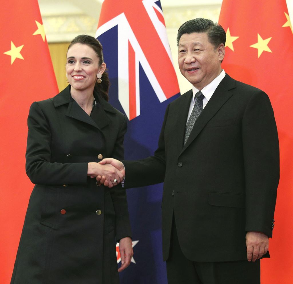 会談前に握手するニュージーランドのアーダン首相(左)と中国の習近平主席=1日、北京(共同)
