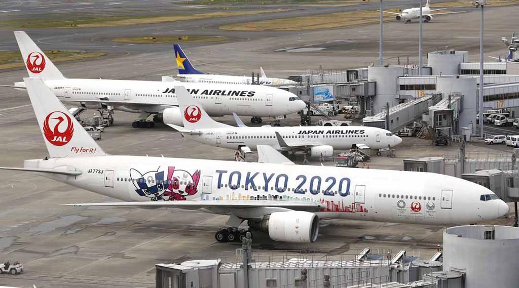 運航が始まった日航の特別機「みんなのJAL2020ジェット」(手前)。東京五輪・パラリンピックの開催を盛り上げようと、公式マスコットや東京の高層ビル群が描かれた=8日午後、羽田空港
