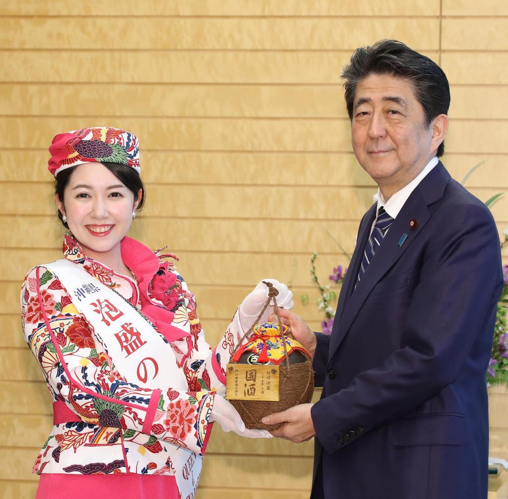 泡盛の女王・砂辺由美さん(左)から琉球泡盛の贈呈を受ける安倍晋三首相=8日午後、首相官邸(春名中撮影)