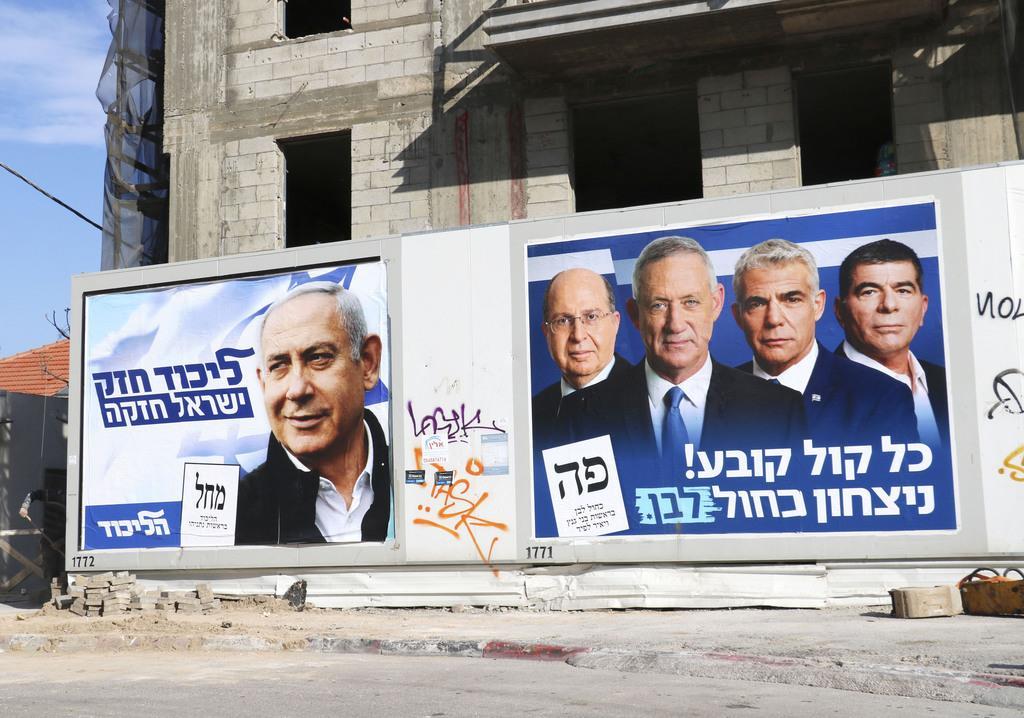 3日、イスラエル中部テルアビブに掲示された選挙ポスター。左がネタニヤフ首相、右がガンツ元軍参謀総長らのポスター(共同)