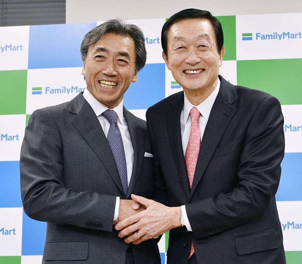 記者会見で握手するファミリーマートの沢田貴司社長(左)とユニー・ファミリーマートHDの高柳浩二社長=10日午後、東京都港区