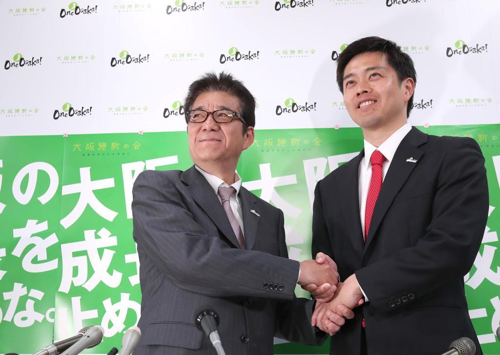 大阪市長選で当選を確実にした日本維新の会の松井一郎代表(左)は、大阪府知事選を制した吉村洋文氏と固く握手を交わした=4月7日、大阪市中央区(彦野公太朗撮影)