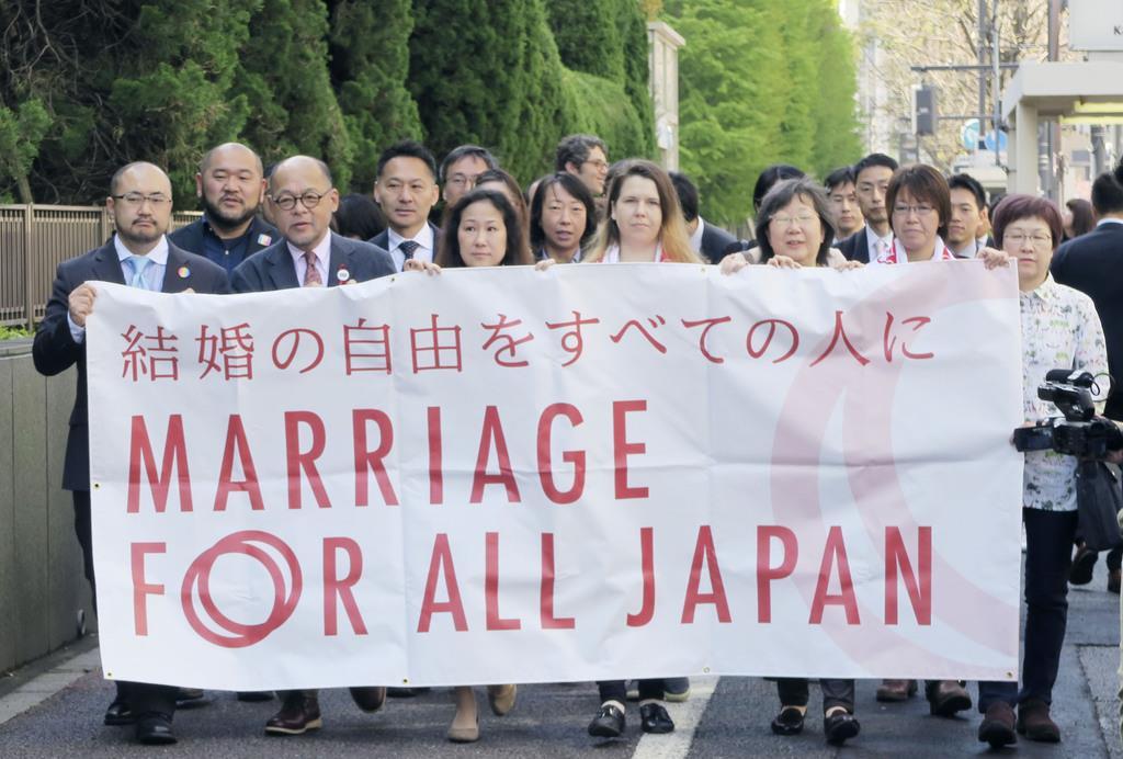 同性婚訴訟の第1回口頭弁論を前に東京地裁へ向かう原告ら=15日午前、東京・霞が関