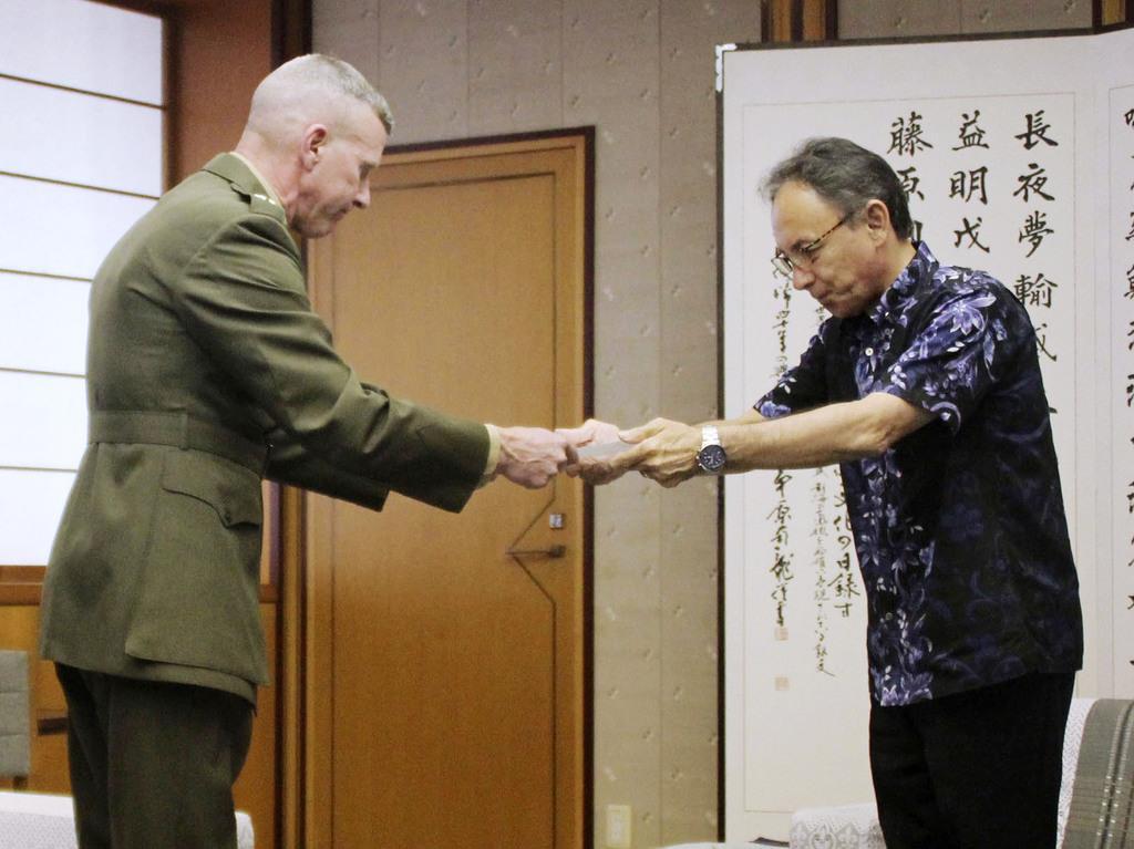 在沖縄米軍トップのエリック・スミス在日海兵隊司令官(左)に抗議文を手渡す沖縄県の玉城デニー知事=15日午後、沖縄県庁