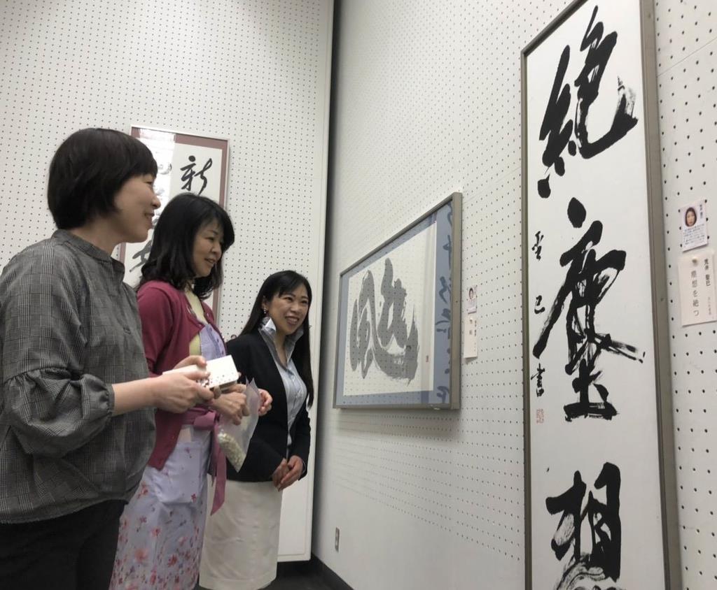 陳列が終わった作品を見る女流書家ら=15日、県立近代美術館(飯嶋彩希撮影)