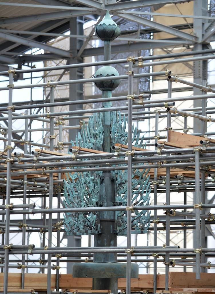 報道陣に公開された、薬師寺東塔の修理現場。頂上にあげられた水煙=15日午後2時6分、奈良市 (安元雄太撮影)