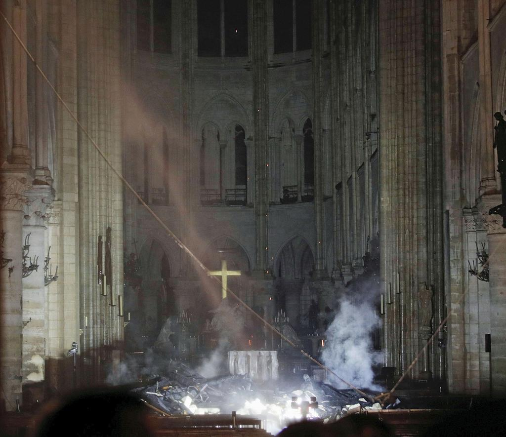 火災で煙が上がるノートルダム寺院の内部=15日、パリ(ロイター)