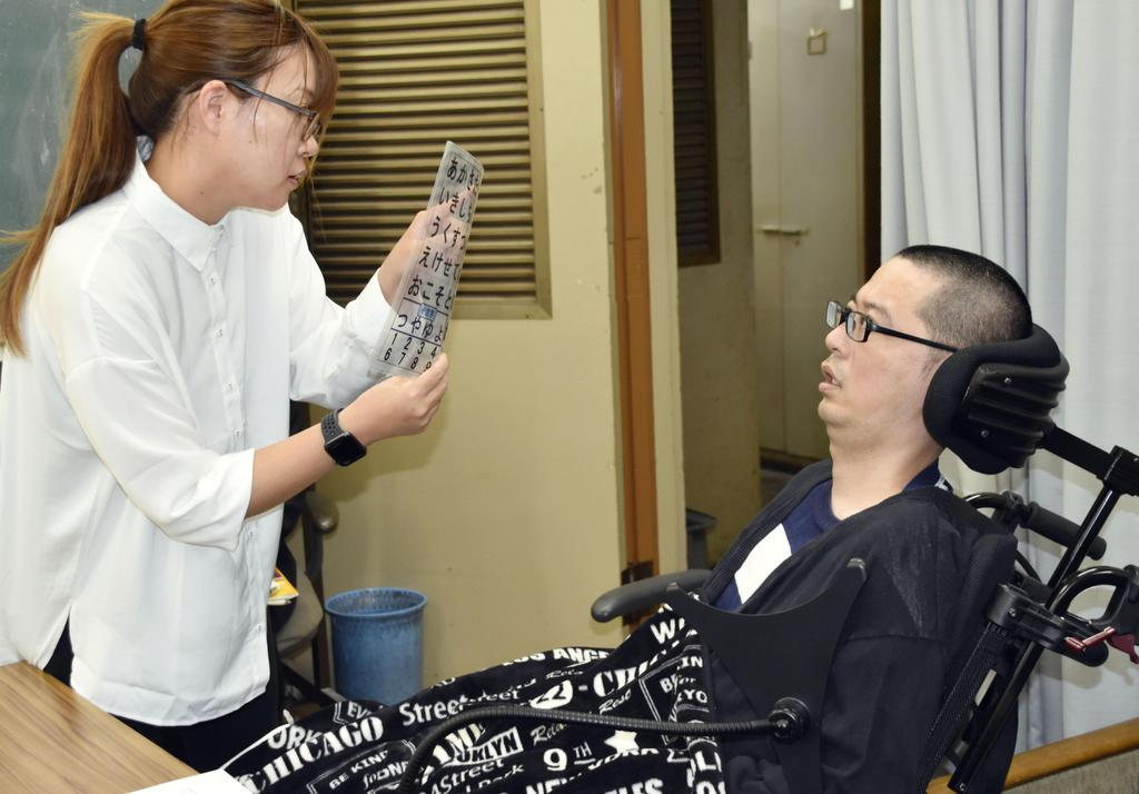 記者会見で、文字盤を通じて質問に答えるALS患者の高田泰洋さん(右)=16日午後、埼玉県庁