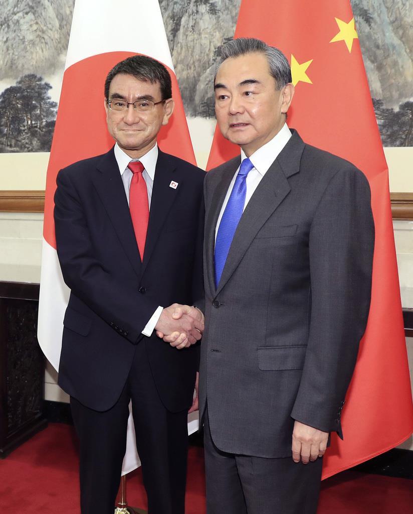 会談を前に中国の王毅国務委員兼外相(右)と握手する河野外相=15日、北京(代表撮影・共同)