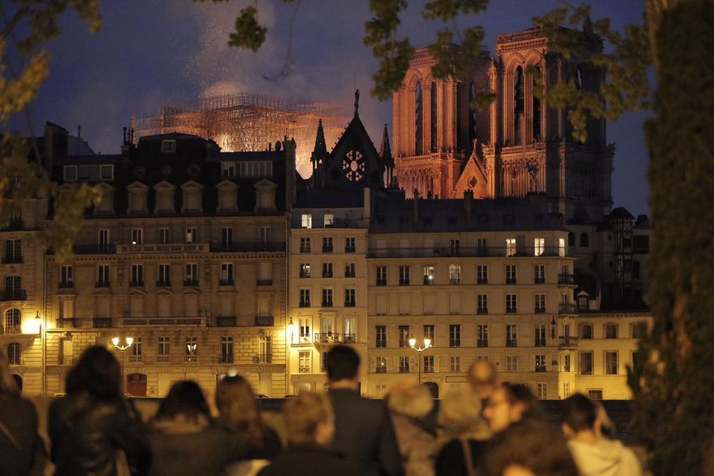 ノートルダム寺院の火災をセーヌ川の対岸から見る市民ら=15日、パリ(共同)