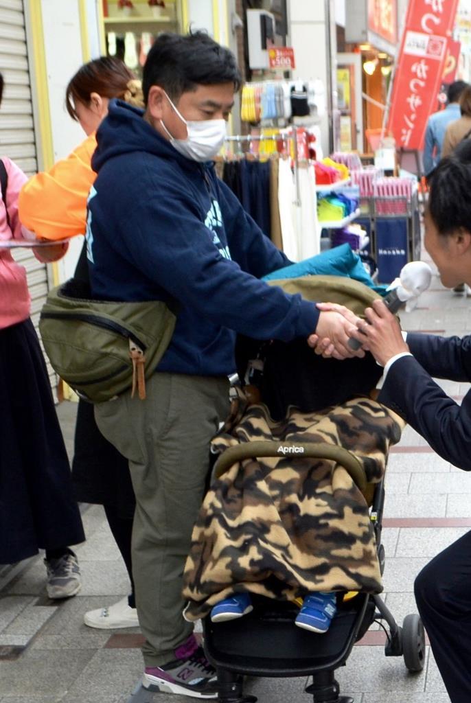 商店街で候補者(右)から手を握られる子供連れの男性=14日、北区(石井那納子撮影)