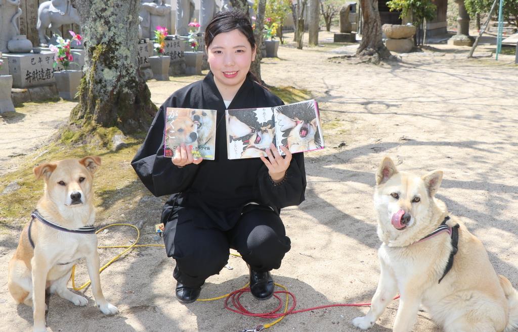 写真集をもつ豊岳由華さん。イヌは右から、こてつ、なむ=岡山県玉野市