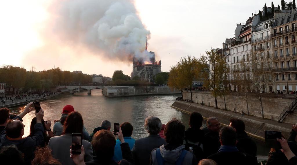煙を上げるノートルダム大聖堂=15日、パリ(ロイター)